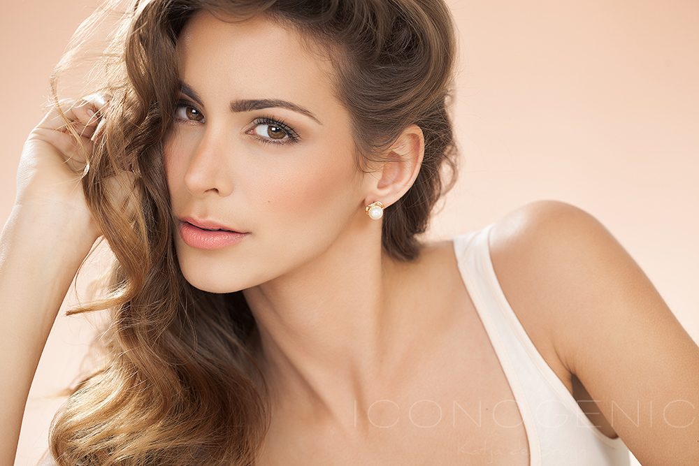 Warm toned portrait of a young woman with beautiful brown hair. Fashion and beauty concept in studio.